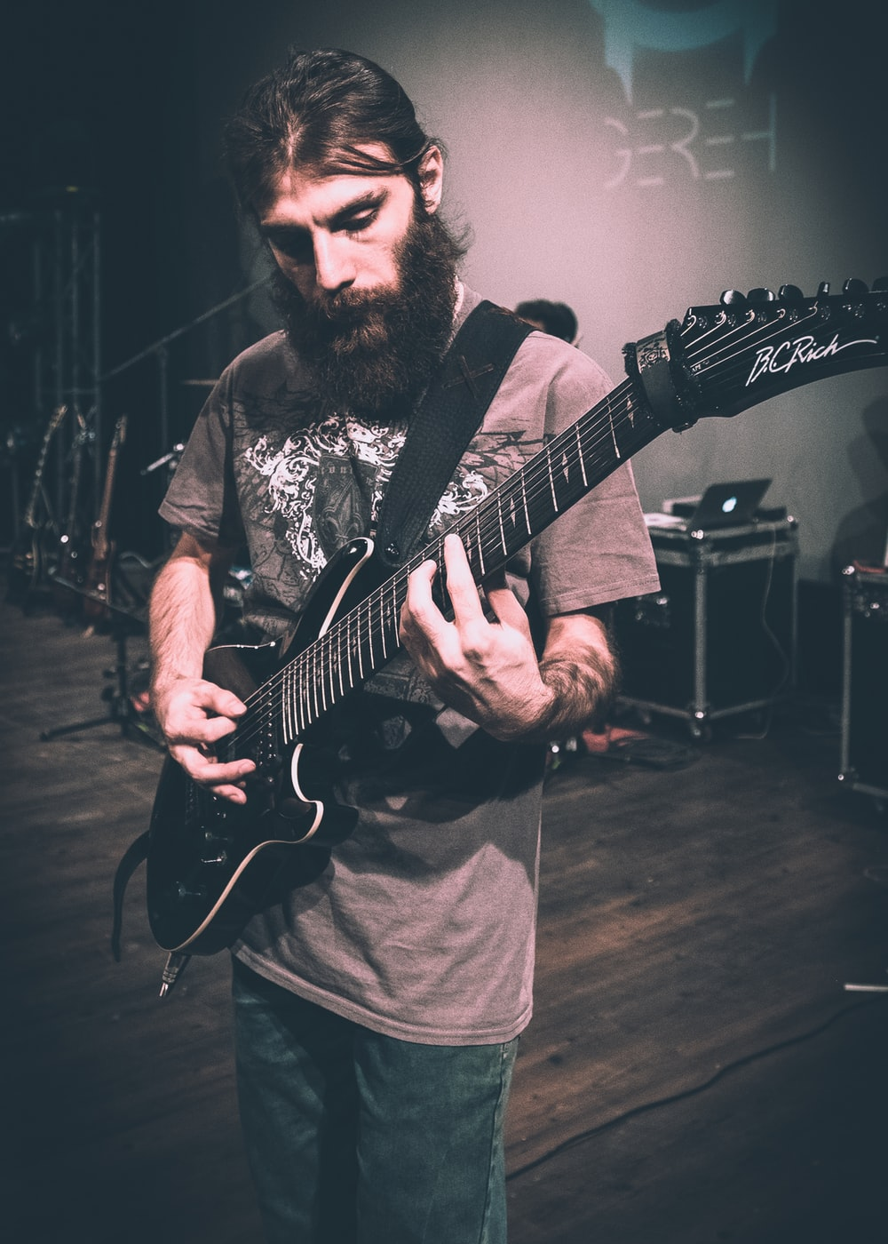 man in gray crew neck shirt playing electric guitar