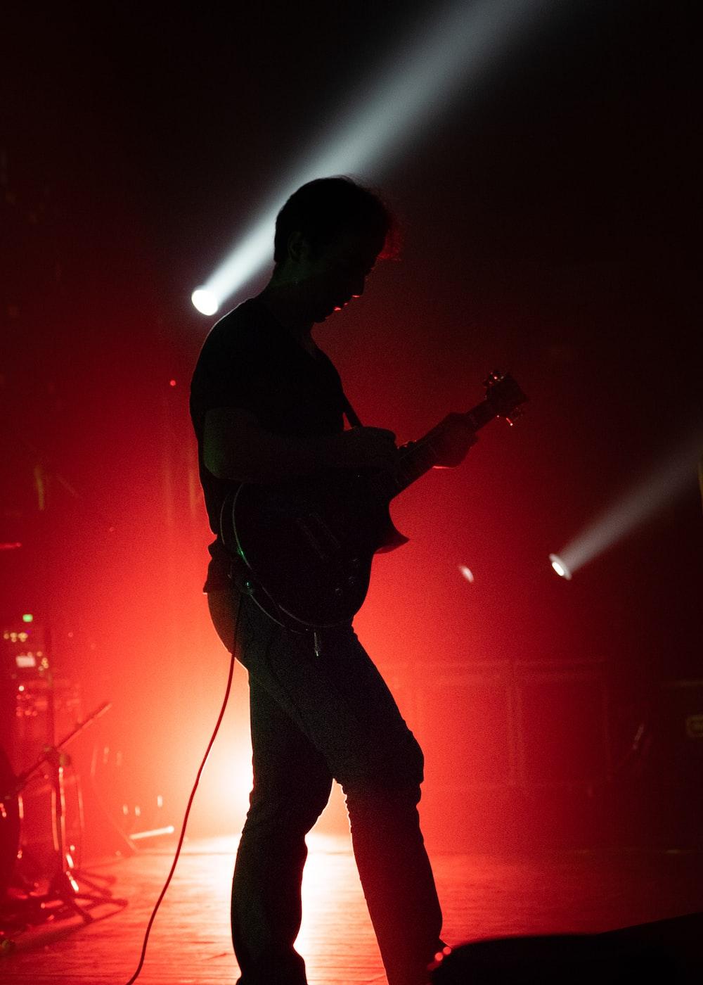 man in black t-shirt playing guitar