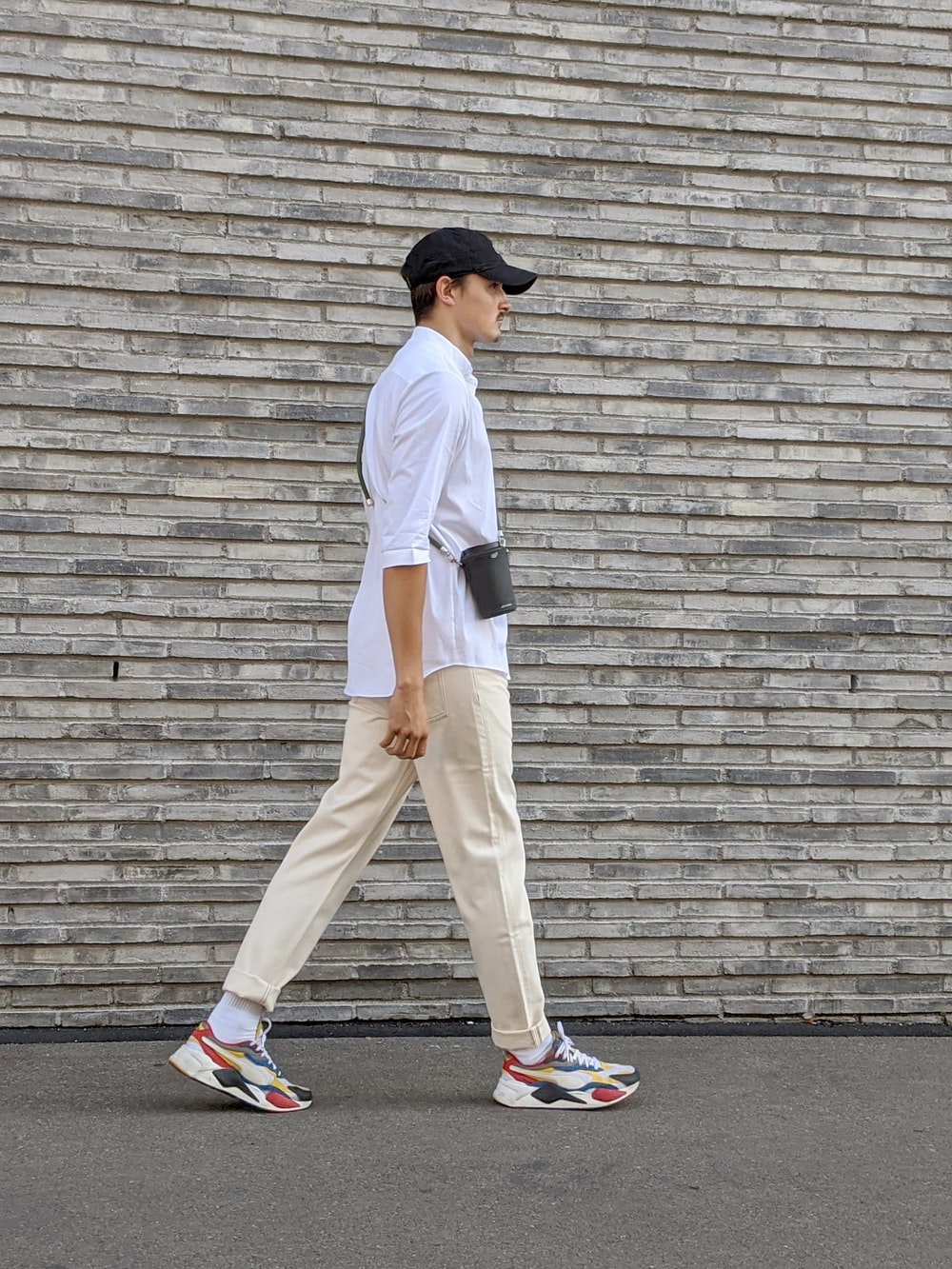 man in white t-shirt and beige pants standing on gray concrete floor