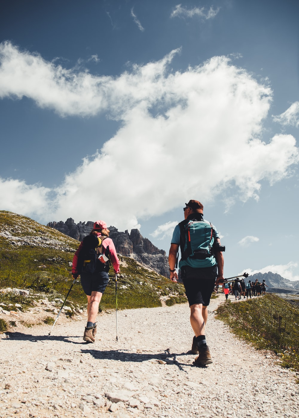 man in green shirt and black shorts with hiking backpack walking on gray sand during daytime