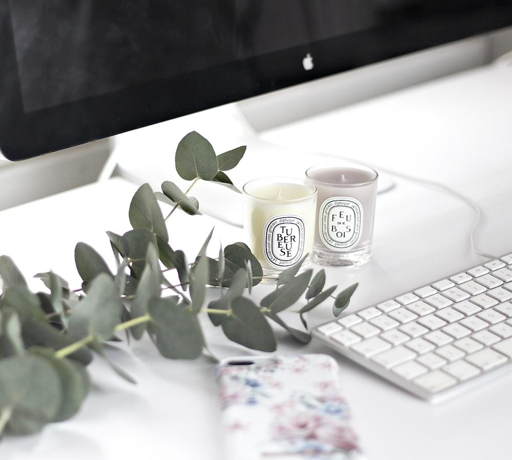 white and black ceramic mug beside white apple keyboard
