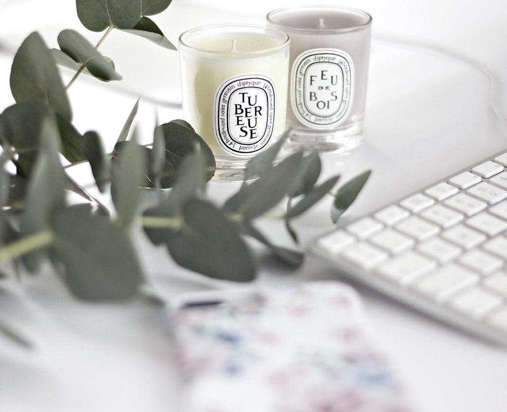 white and black ceramic mug beside white computer keyboard