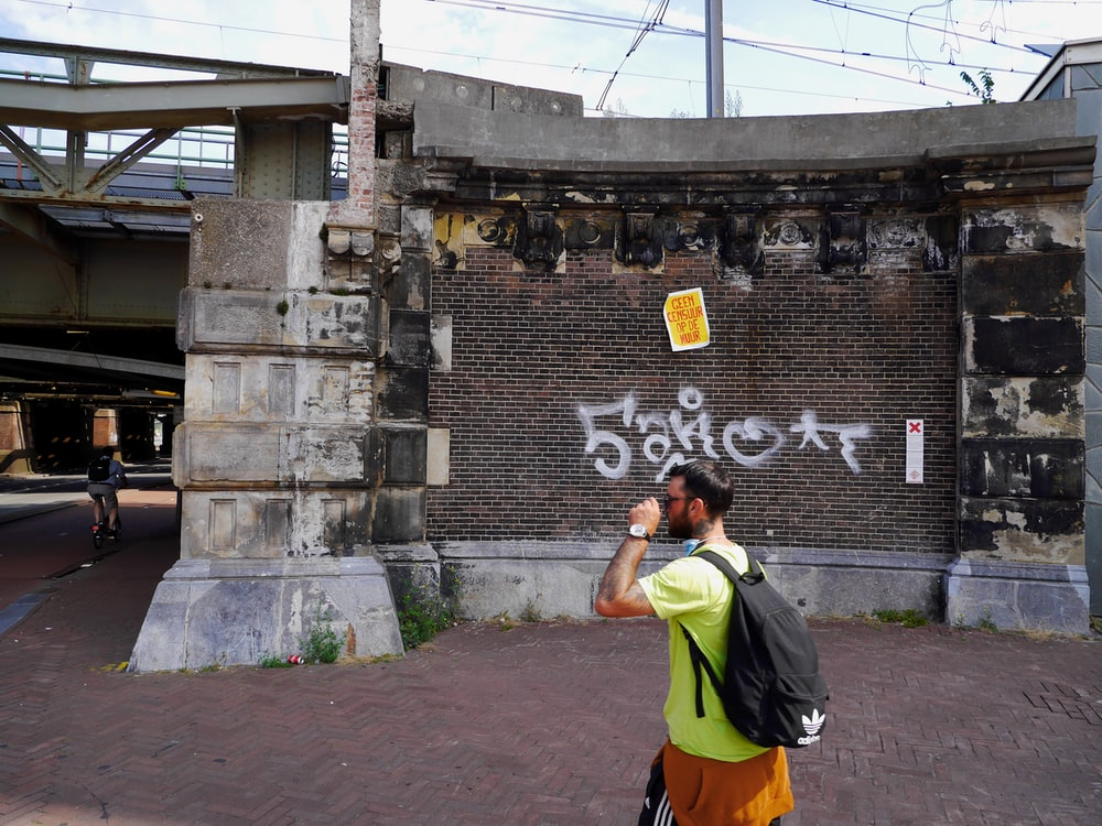 man in yellow shirt and gray backpack standing beside gray concrete wall during daytime