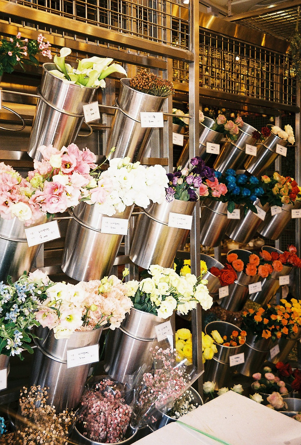 pink and white flowers in stainless steel containers