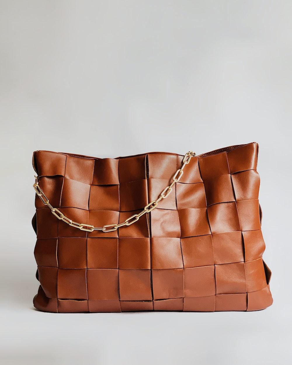 brown leather handbag on white surface