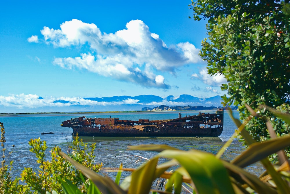 brown ship on sea under blue sky and white clouds during daytime