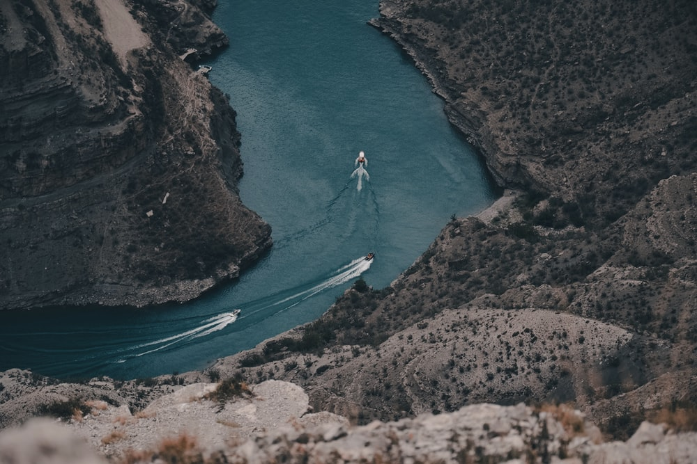 aerial view of person riding on white boat on blue sea during daytime