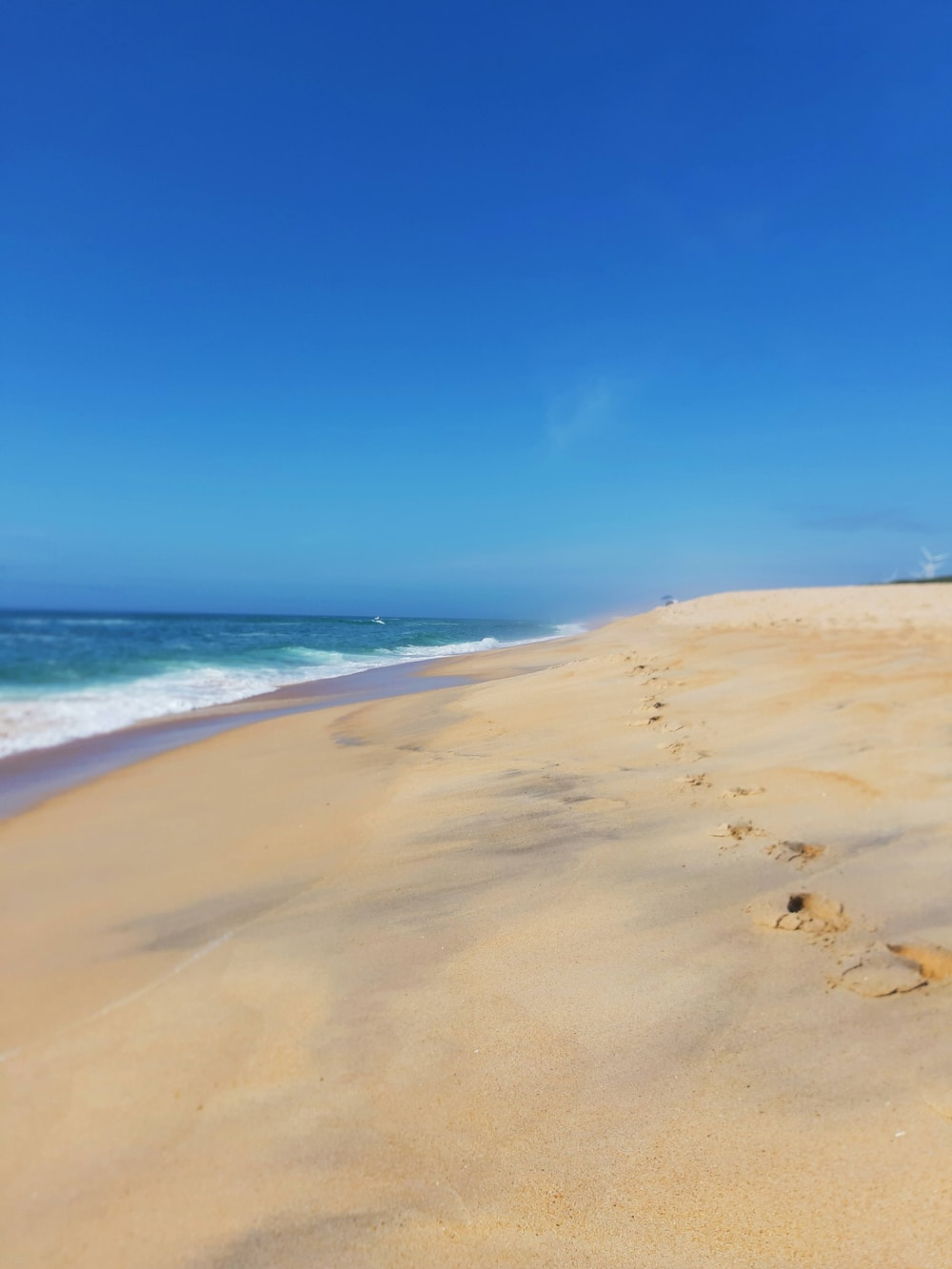 brown sand beach under blue sky during daytime