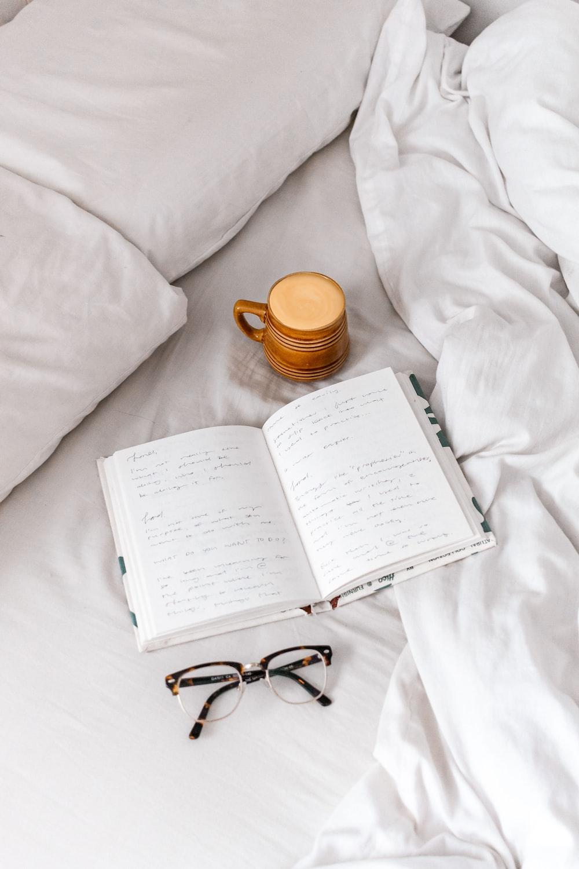 black framed eyeglasses on white book page beside brown ceramic mug on white textile