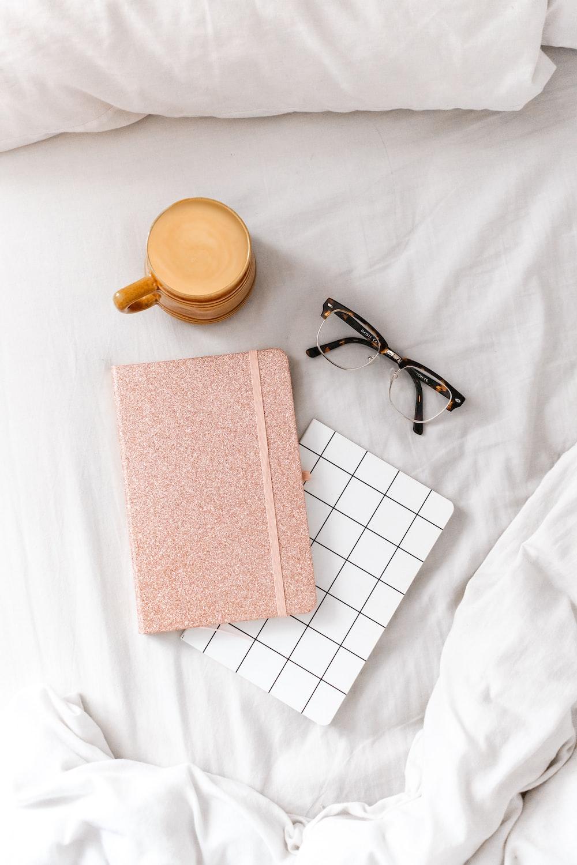 black framed eyeglasses beside brown book on white textile