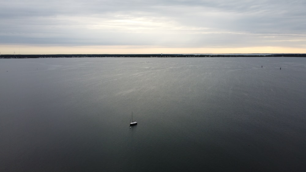 boat on calm sea under white clouds during daytime