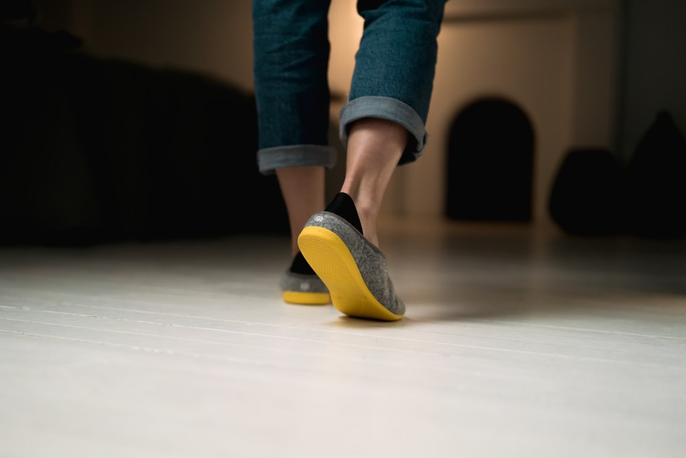 person in blue denim jeans and yellow and blue socks