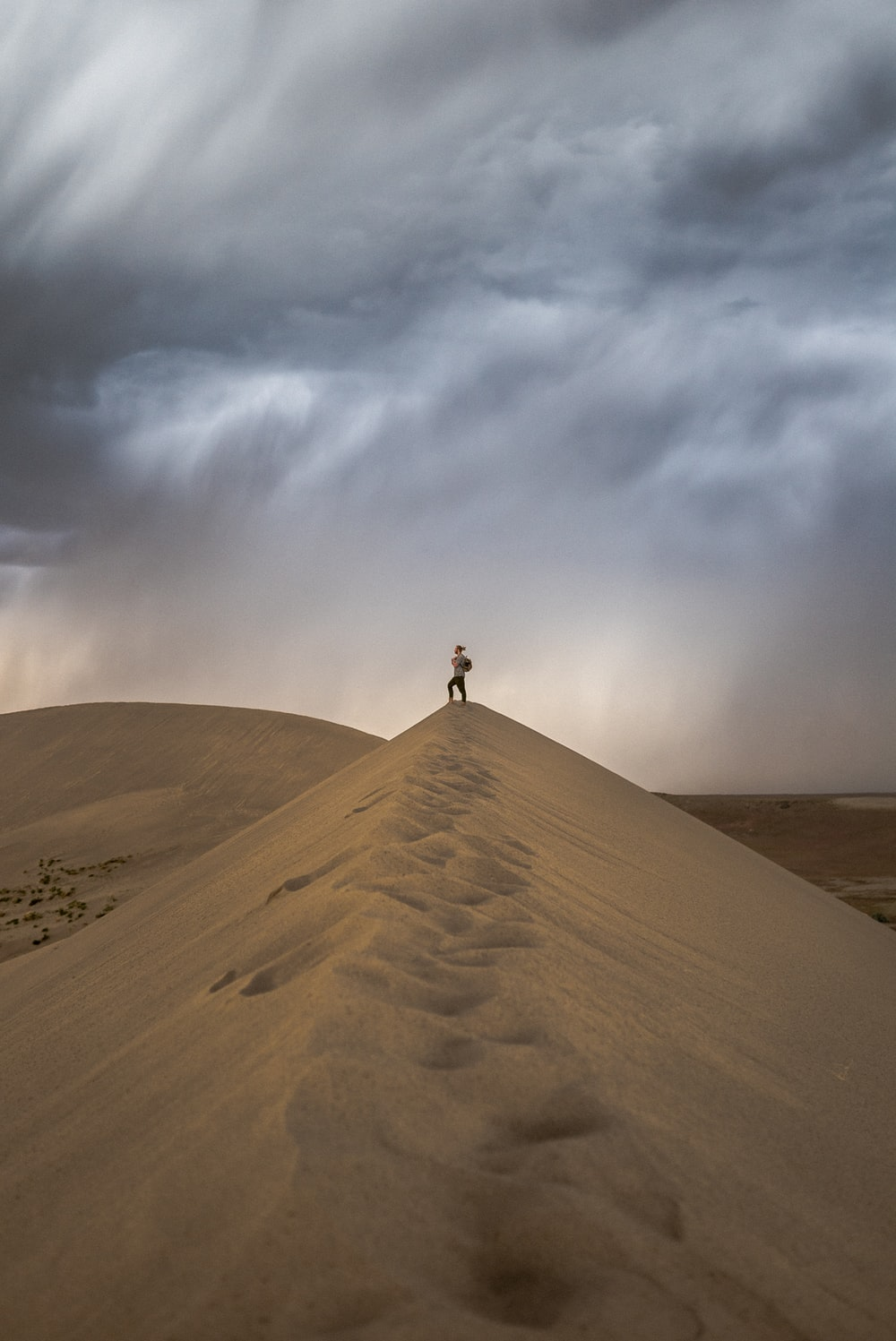 person standing on brown sand under white clouds during daytime