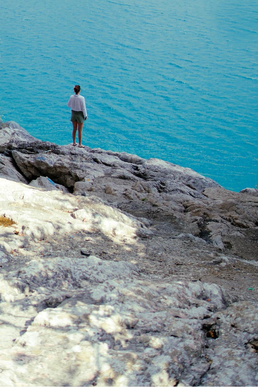 man in white shirt standing on white rock near blue sea during daytime