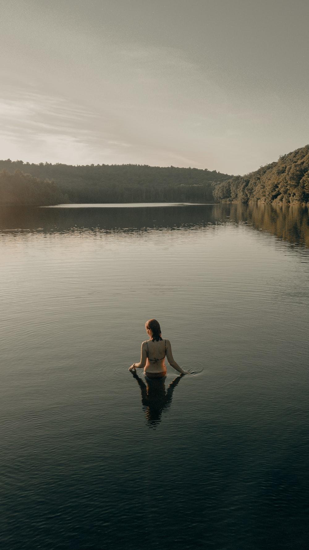woman in black bikini sitting on rock near body of water during daytime