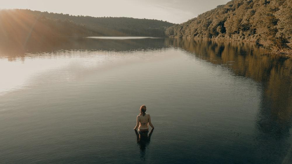 woman in black dress standing on lake during daytime