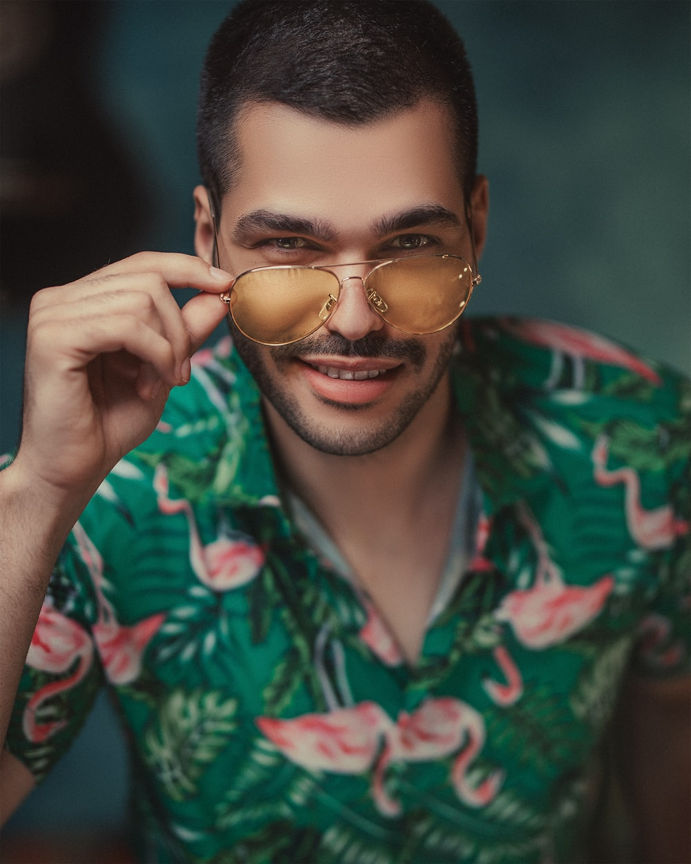 man in green and red floral button up shirt wearing gold framed sunglasses