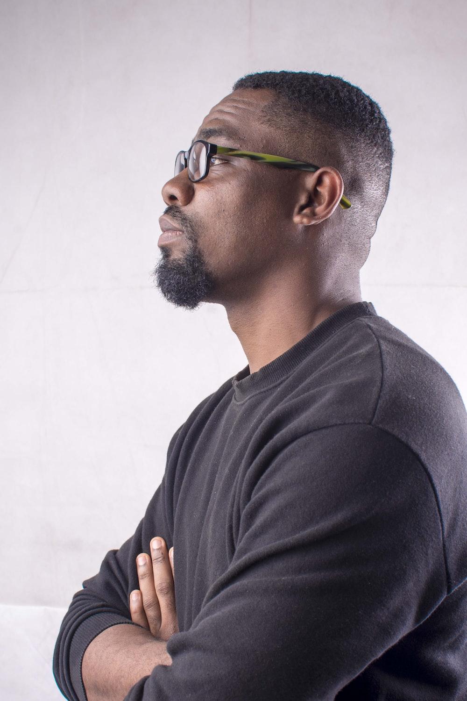 man in black crew neck long sleeve shirt wearing eyeglasses