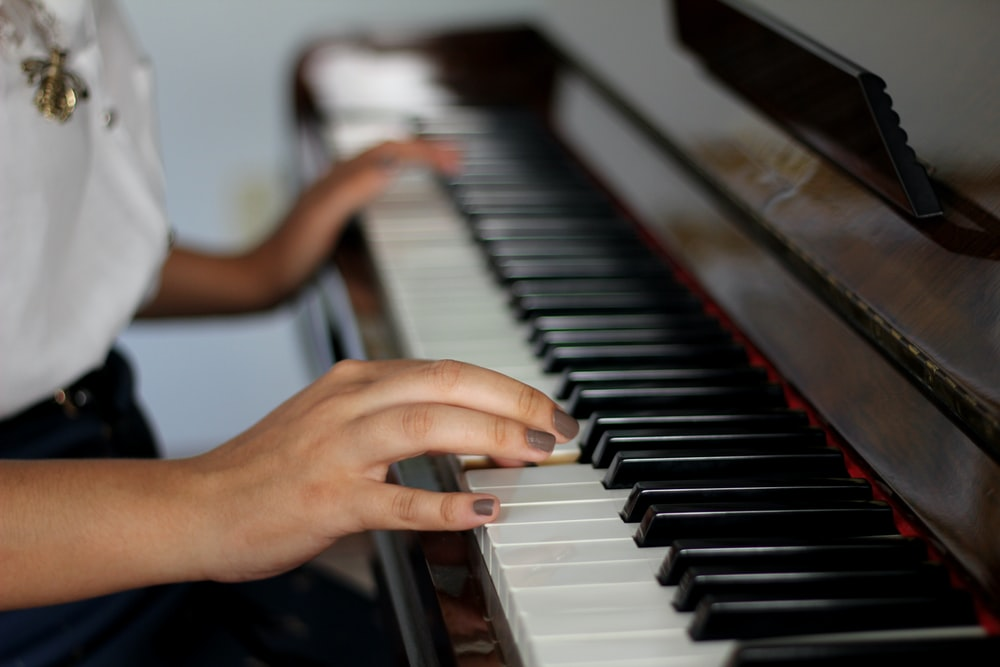 person playing piano in close up photography