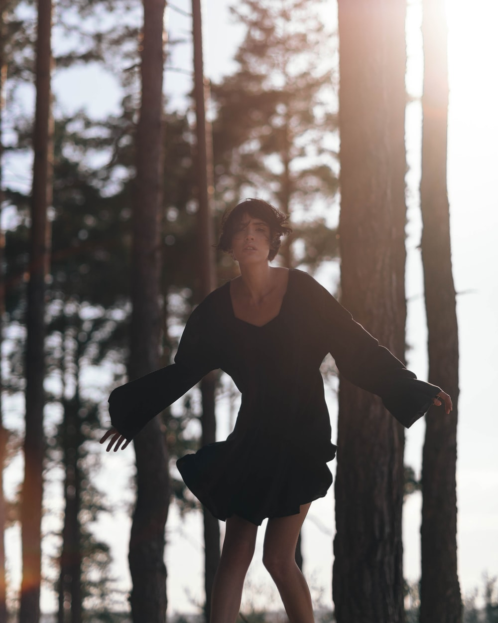 woman in black long sleeve shirt standing on brown wooden post during daytime