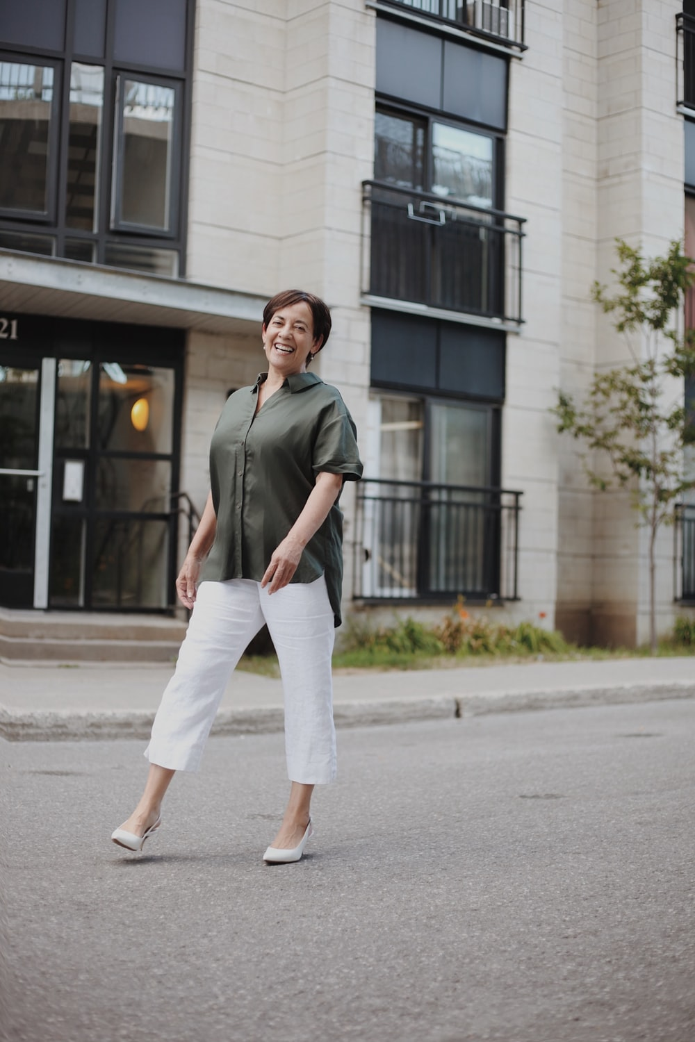 man in green button up shirt and white pants standing on sidewalk during daytime