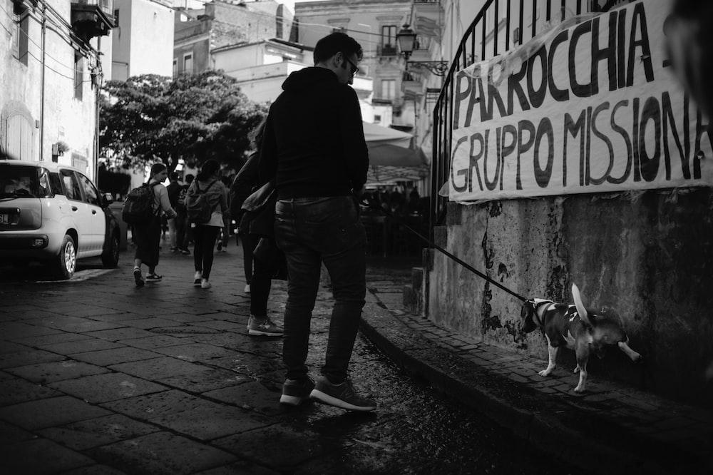 man in black jacket and blue denim jeans walking on sidewalk with dog