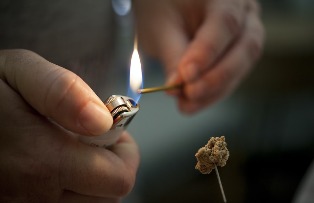 person holding lighted lighter with fire