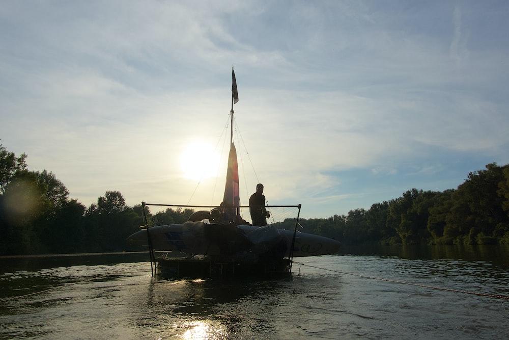 man riding on boat on lake during daytime