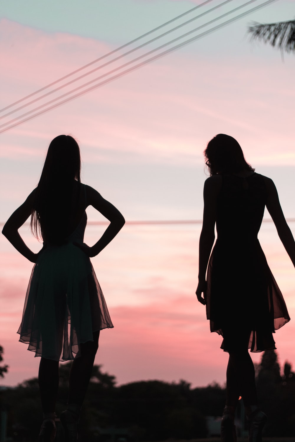 2 women in dress standing on beach during sunset