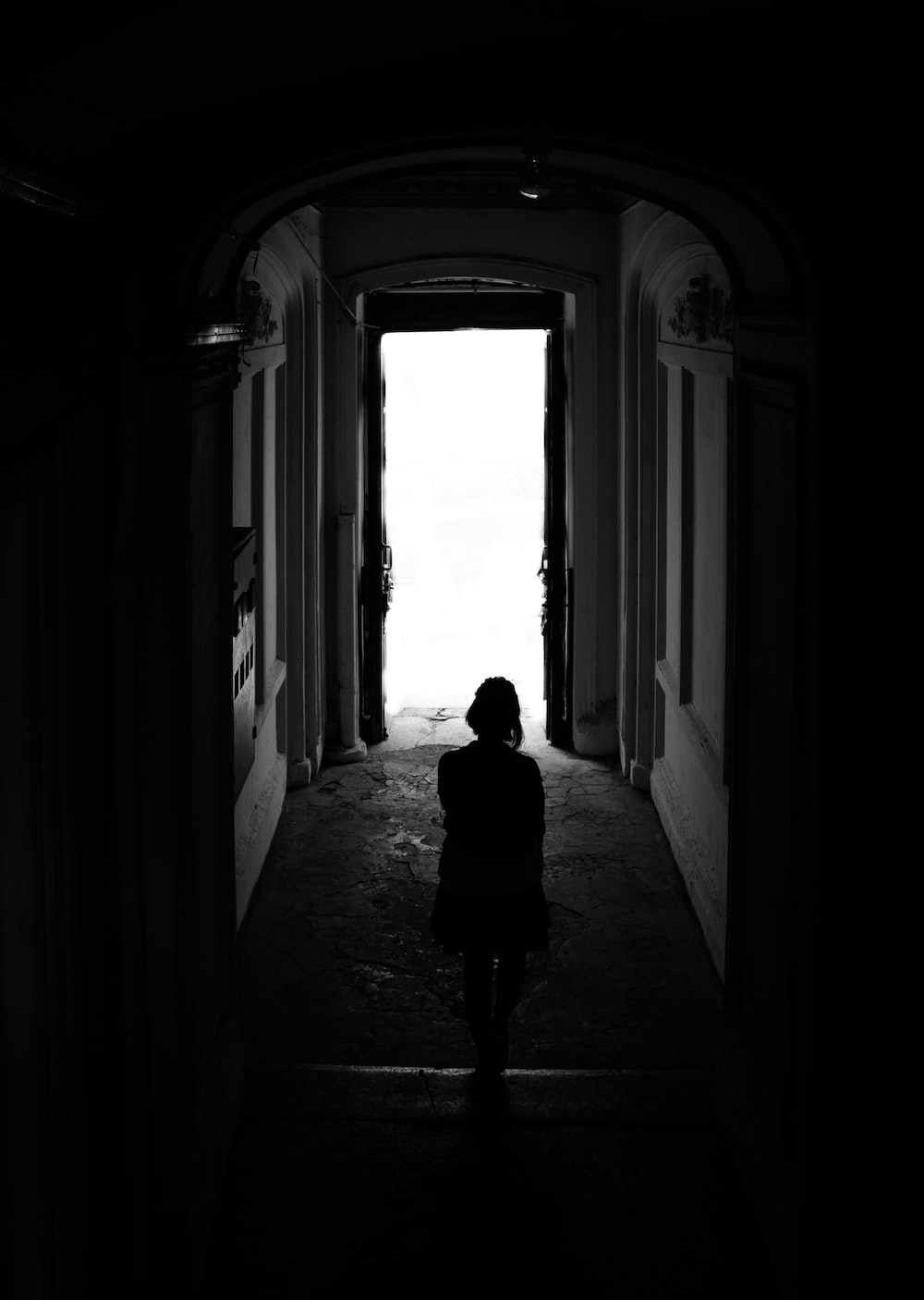 silhouette of woman walking on hallway