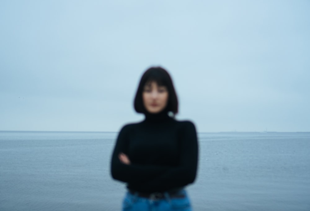 woman in black long sleeve shirt and blue denim jeans standing on beach during daytime