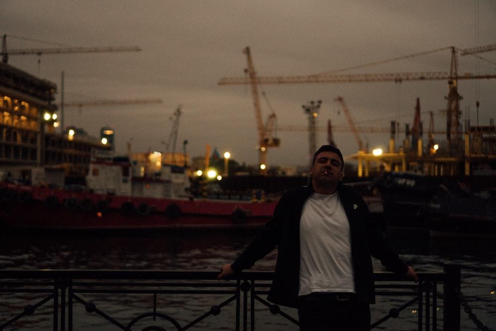 woman in black jacket standing on bridge during night time