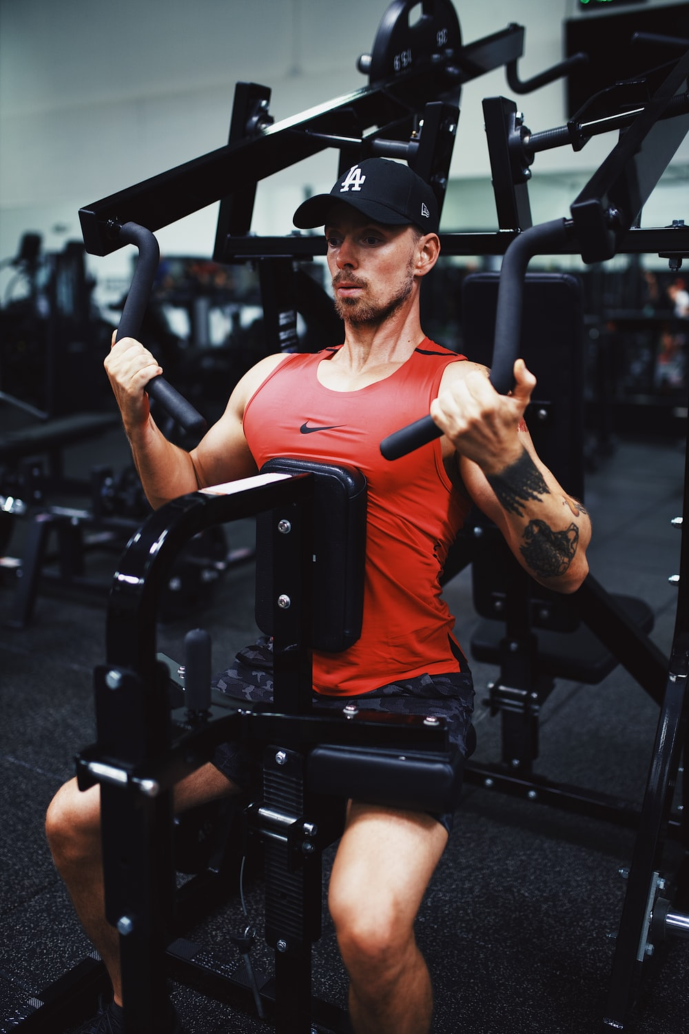 man in orange crew neck t-shirt and black fitted cap sitting on black stationary bike