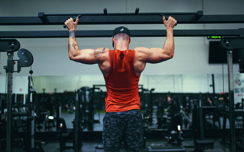 man in red tank top and black shorts holding black and silver barbell