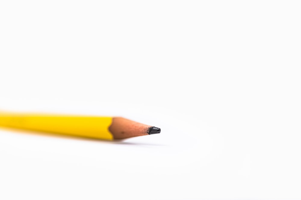 yellow pencil on white surface