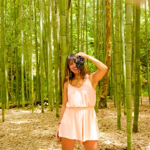 woman in pink sleeveless dress standing on forest during daytime