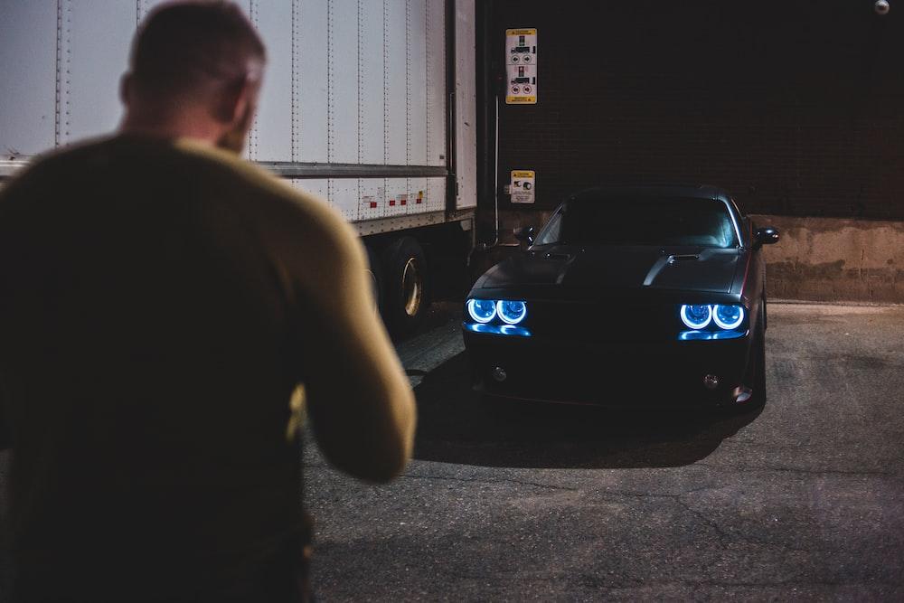 man in black t-shirt standing beside blue car during nighttime