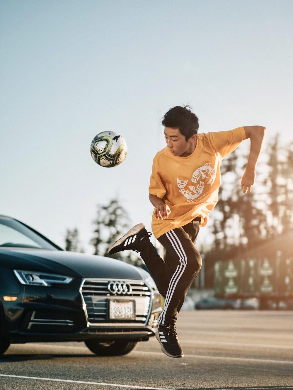 man in orange crew neck t-shirt and black shorts playing soccer during daytime