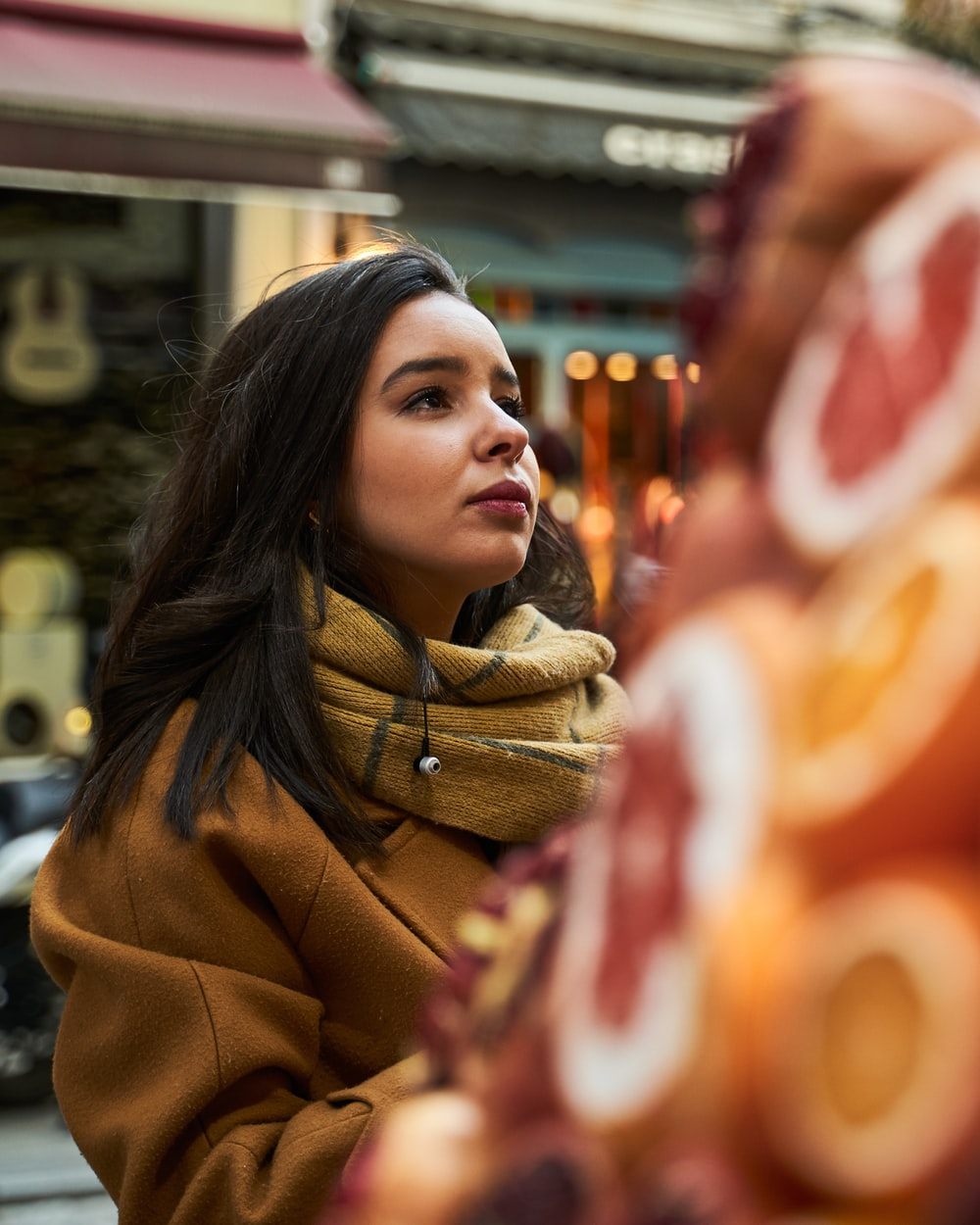 woman in brown scarf and brown coat standing near store during daytime