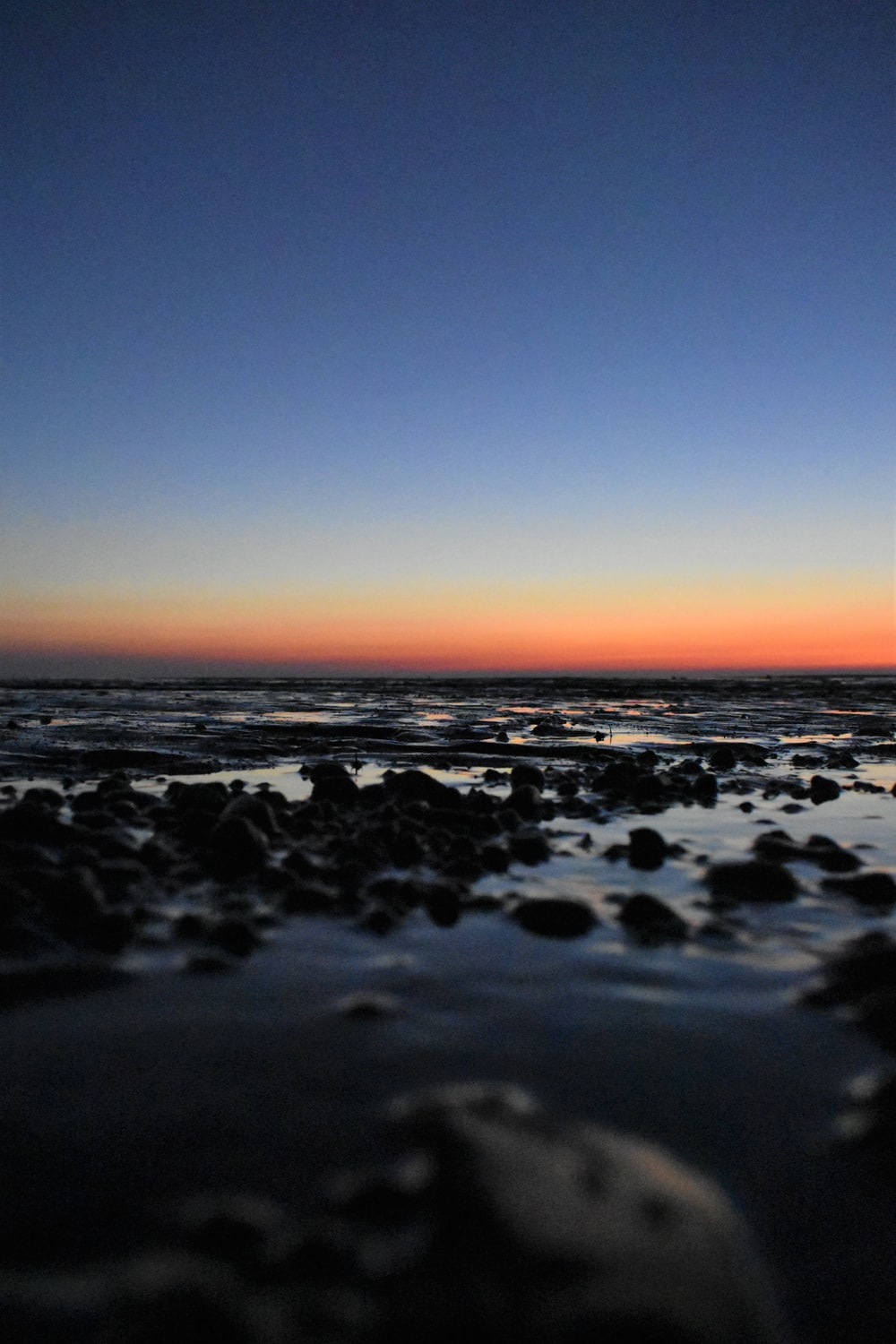 black rocks on the beach during sunset