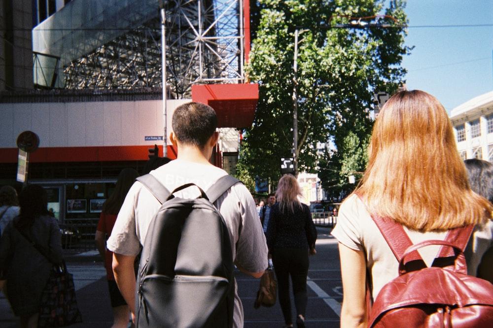 man in white shirt standing beside woman in pink shirt