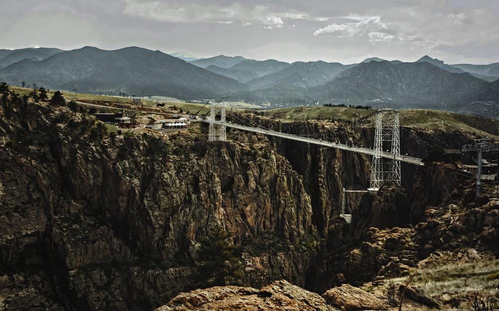 white bridge over the mountain during daytime