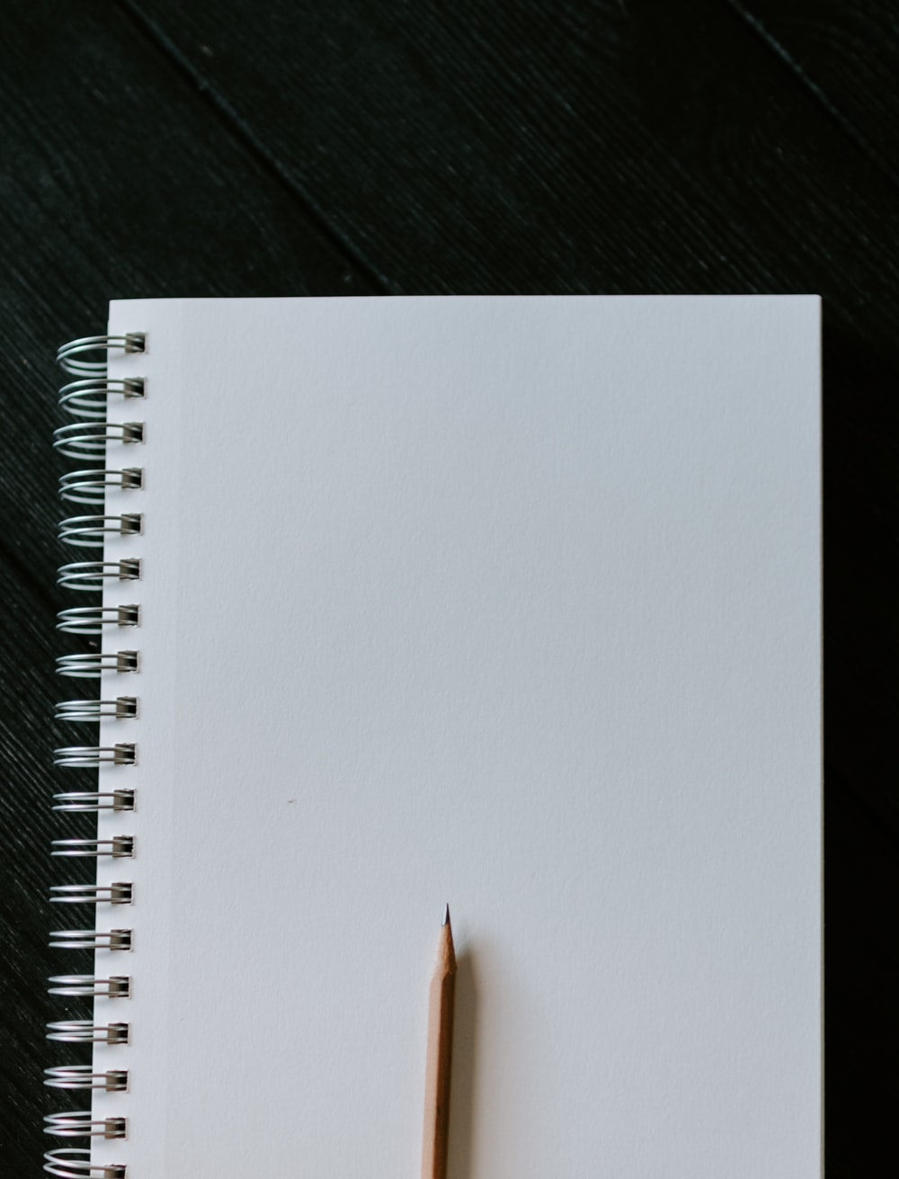 white spiral notebook on black wooden table
