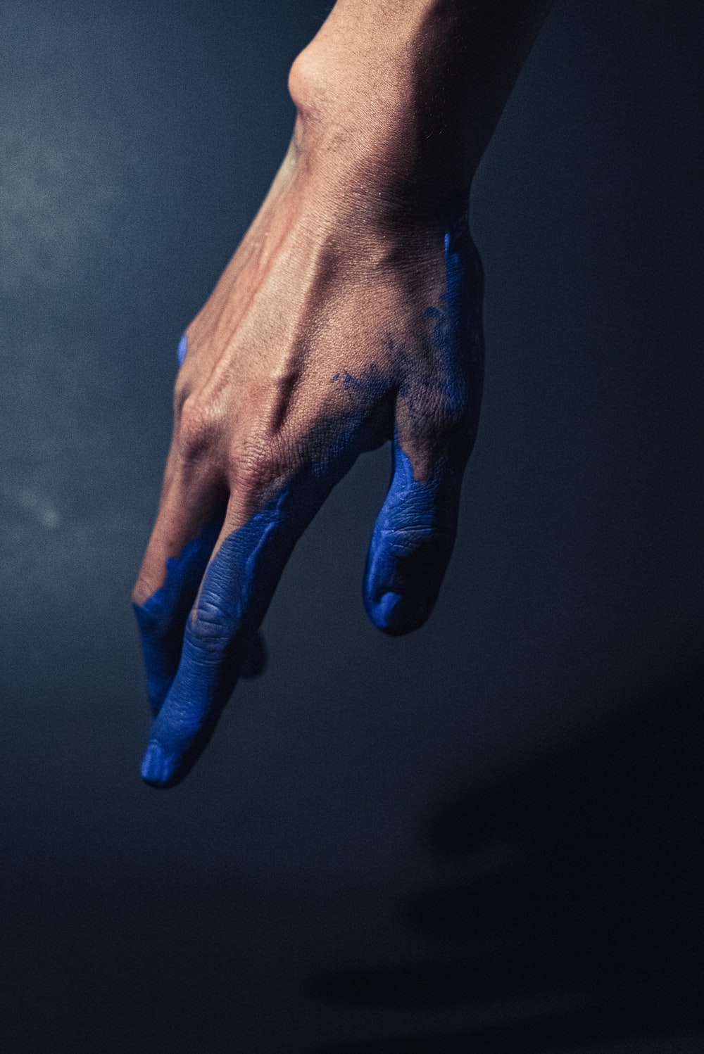 persons left hand with blue nail polish