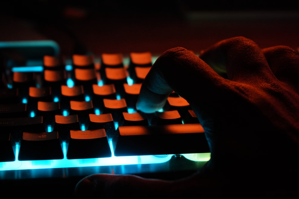 persons hand on blue lighted computer keyboard