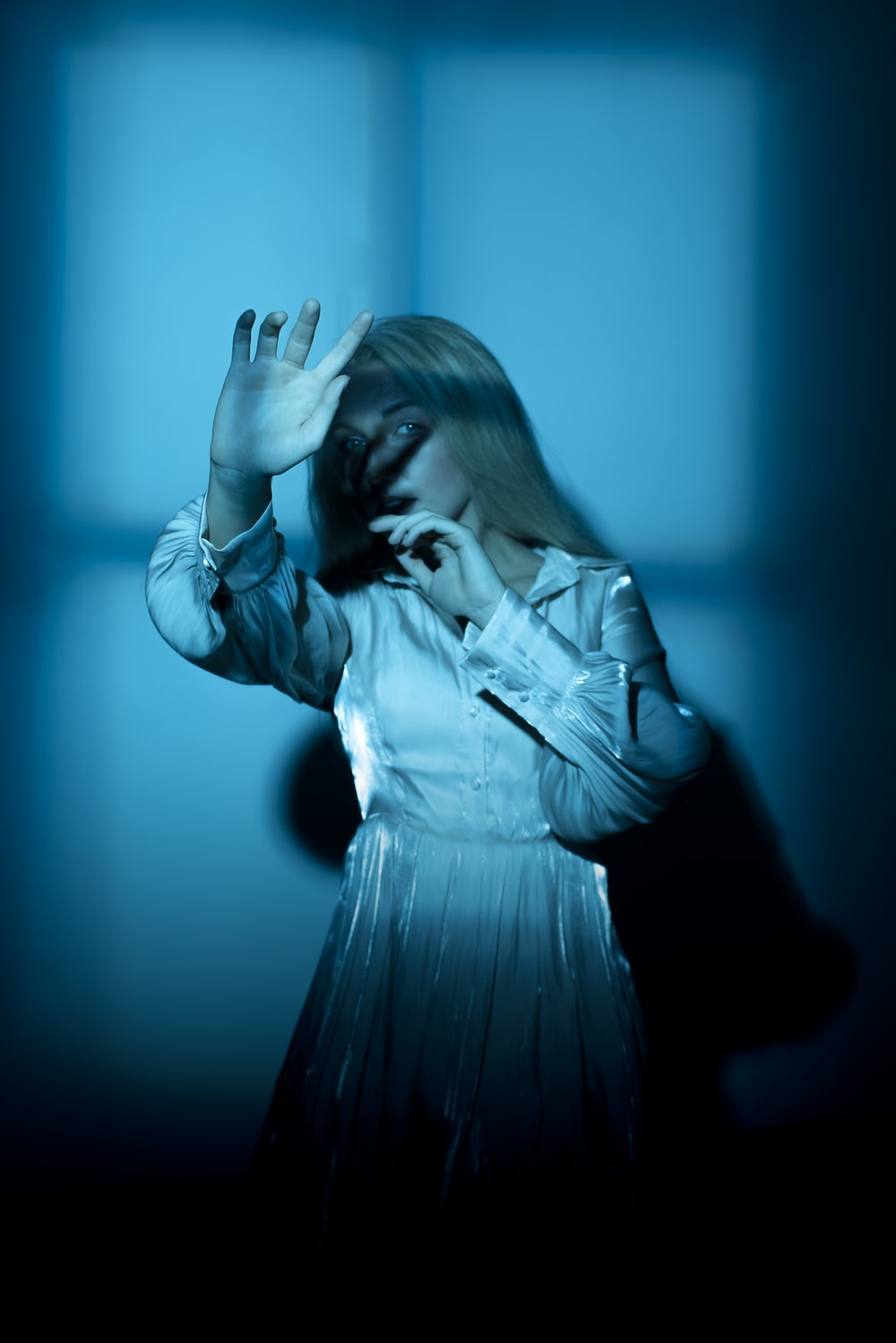 woman in white dress shirt covering her face with her hands