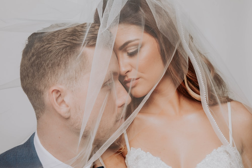 woman in white wedding dress kissing woman in white wedding dress