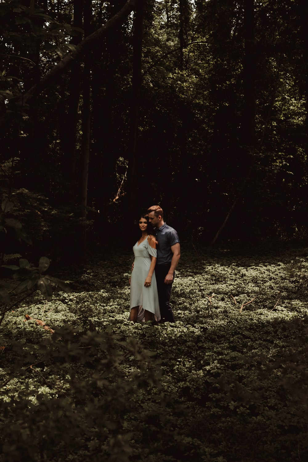 man and woman standing on forest during daytime