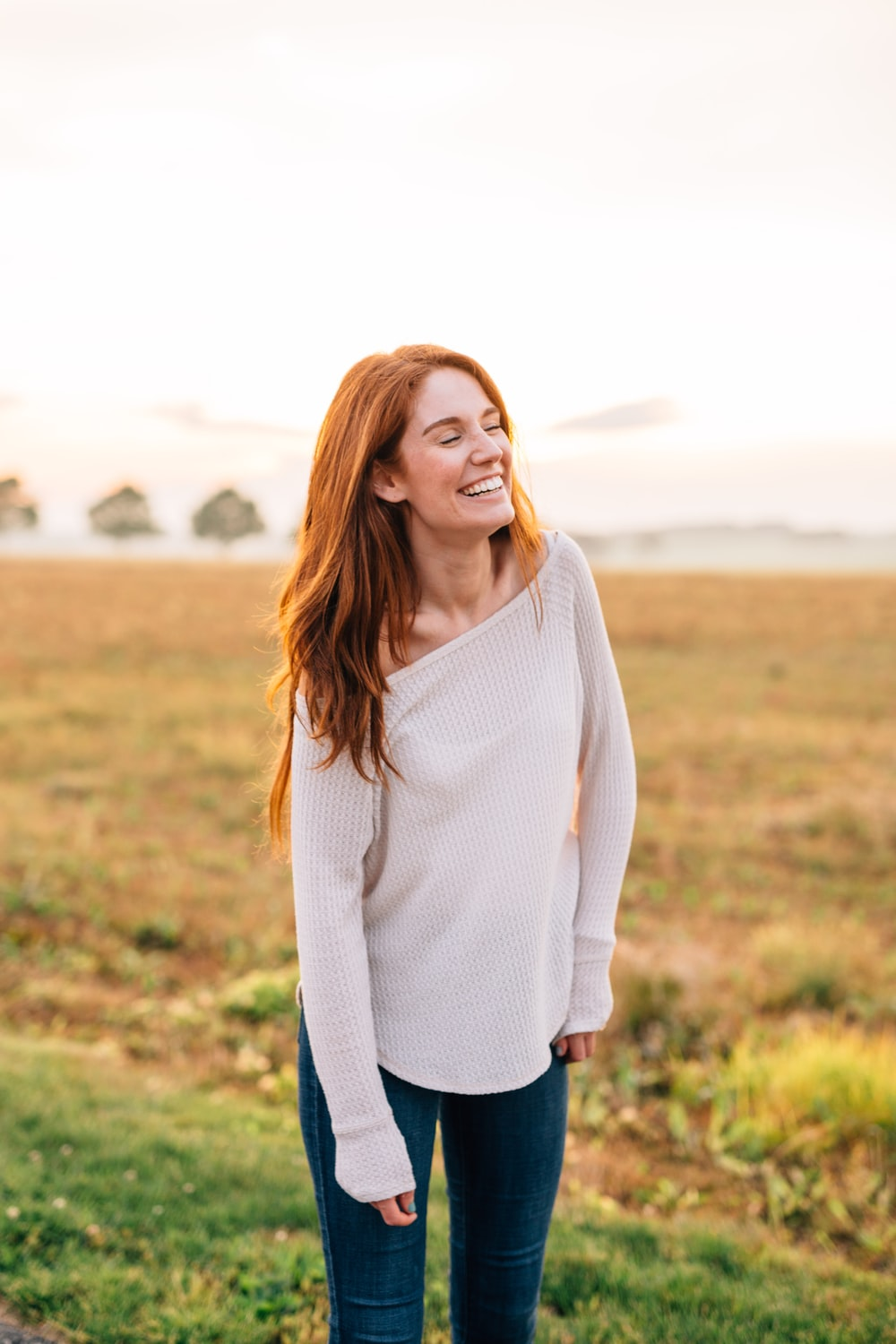 woman in white long sleeve shirt and blue denim jeans standing on green grass field during