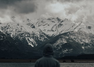 man in gray hoodie standing near body of water and snow covered mountain during daytime